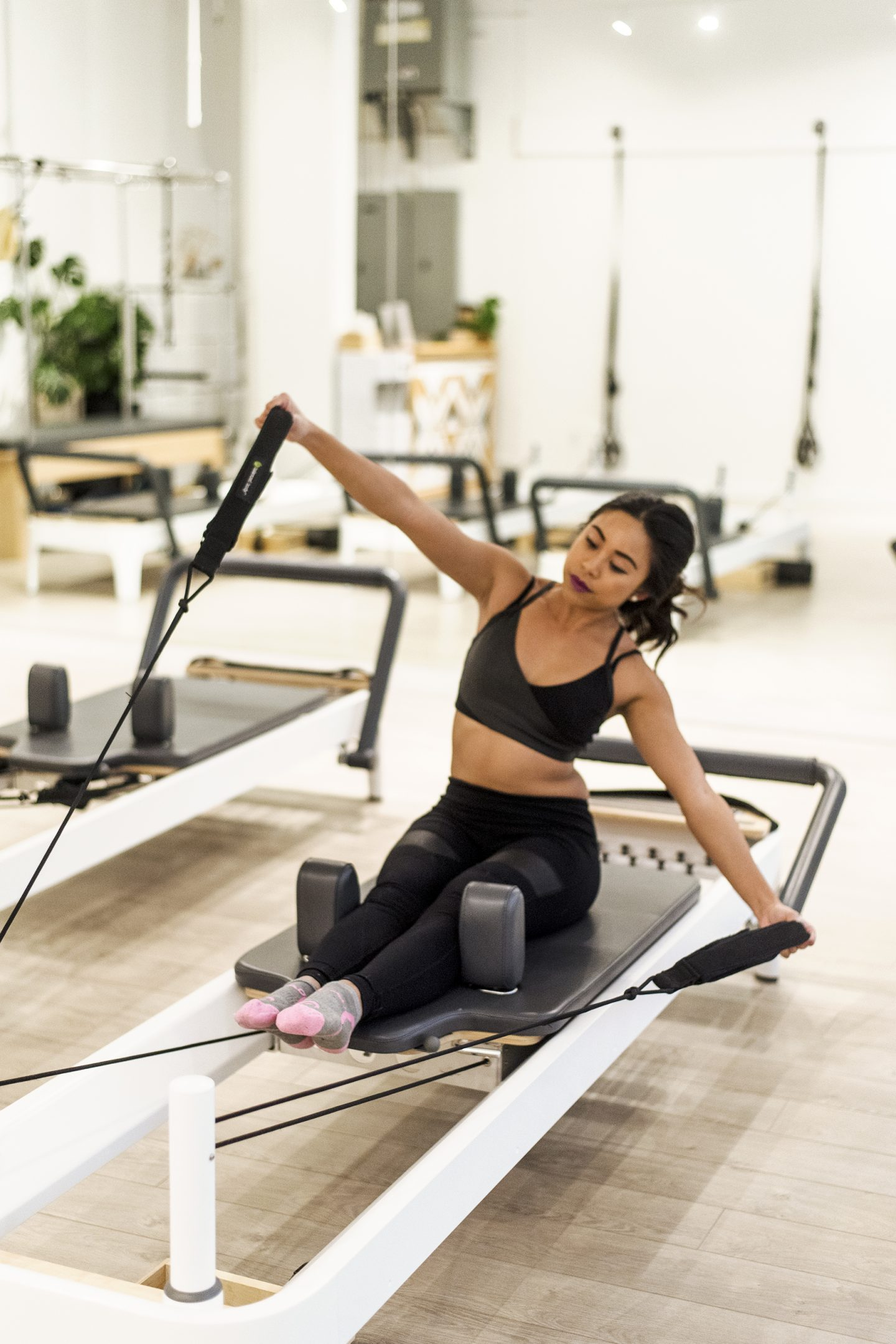 Sitting on the carriage of the reformer - reformer pilates